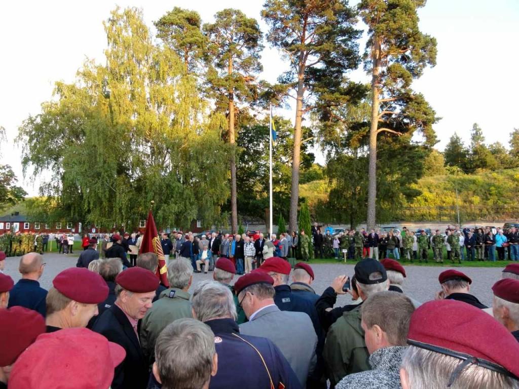 Jubilarerna från årskurs 52/53 skymtas när de är uppställda framför podiet.